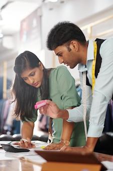 Ernsthafte junge indische schneider zählen den preis des kleidungsstücks, an dem sie arbeiten