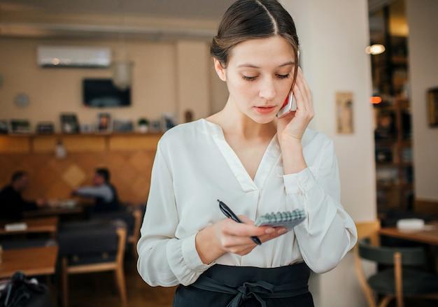 Ernsthafte junge kellnerin stehen in zurückhaltung und telefonieren