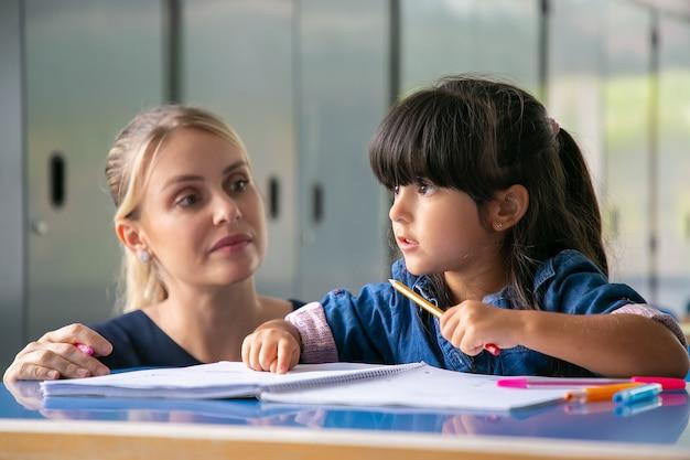 Ernsthafte junge lehrerin, die dem grundschulmädchen hilft, ihre aufgabe zu erfüllen