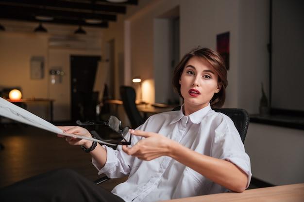 Ernsthafte junge modedesignerin, die eine brille hält und sich skizzen im büro ansieht