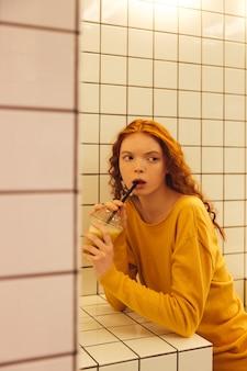Ernsthafte junge rothaarige lockige dame, die im café sitzt