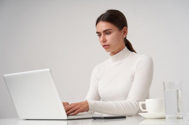 Ernsthafte junge schöne brünette frau, die bildschirm mit konzentriertem gesicht beim schreiben von text auf tastatur betrachtet und am tisch über weißer wand sitzt