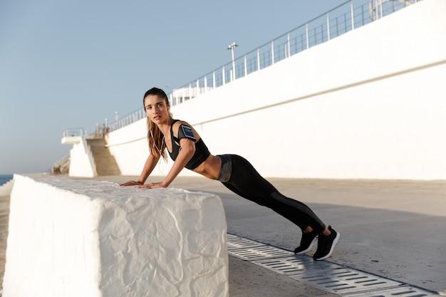 Ernsthafte junge sportfrau, die musik hört, macht sportübungen.