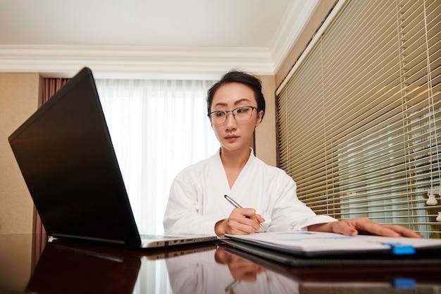 Ernsthafte junge unternehmerin, die ein dokument auf dem laptop-bildschirm liest und den verkaufsbericht analysiert