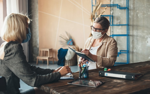 Ernsthafte kaukasische ältere frau mit medizinischer maske auf gesicht und brille diskutiert mit einem klienten zu hause, während sie etwas in das buch schreiben