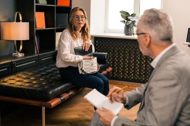 Ernsthafte kaukasische blonde frau mit einer handtasche auf den knien, die auf der couch vor ihrem psychoanalytiker sitzt