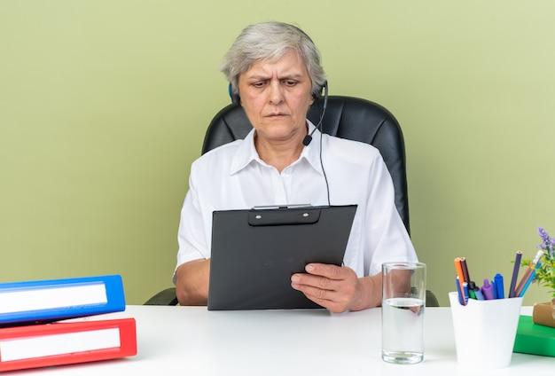 Ernsthafte kaukasische call-center-betreiberin auf kopfhörern, die am schreibtisch mit bürowerkzeugen sitzen und die zwischenablage einzeln auf grüner wand halten und betrachten