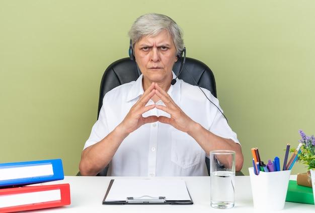 Ernsthafte kaukasische call-center-betreiberin auf kopfhörern, die mit bürowerkzeugen mit den händen zusammen am schreibtisch sitzen