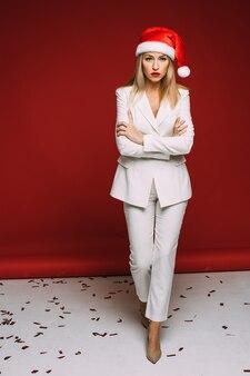 Ernsthafte kaukasische frau im weißen anzug mit einem roten und weißen hut auf ihrem kopf