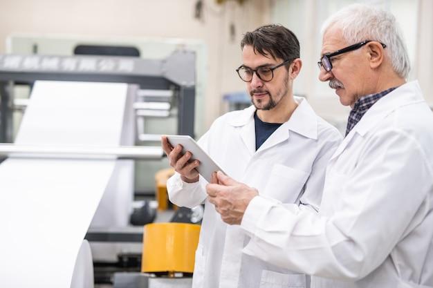Ernsthafte kollegen in weißen kitteln mit tablet-app bei der inspektion von druckmaschinen im werk
