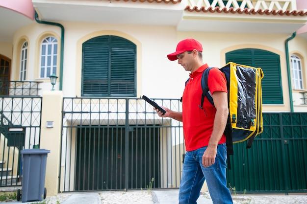 Ernsthafte kurierbeobachtungsadresse auf tablett, zwischenablage haltend und gelbe thermotasche lieferbote in roter kappe, die expressbestellung zu fuß liefert. lieferservice und online-shopping-konzept