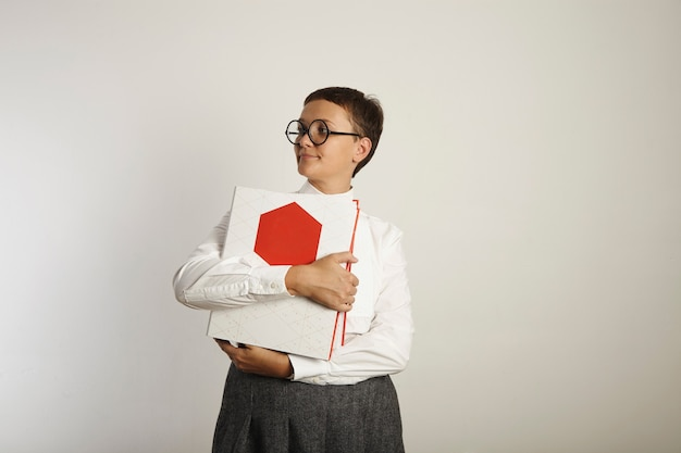 Ernsthafte lehrerin in langweiligen kleidern, die hoch auf weißer wand stehen und wegschauen und leuchtend rote und weiße bindemittel umarmen