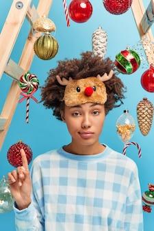 Ernsthafte lockige frau bekommt idee, wie man neujahr feiert, hebt zeigefinger trägt lässige hauskleidung posen