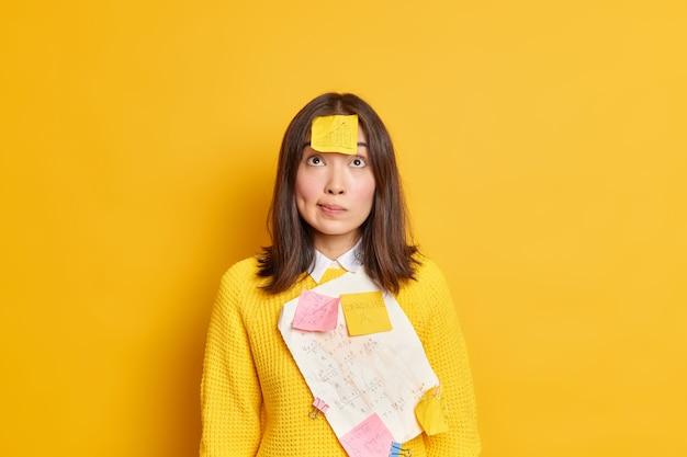 Ernsthafte managerin, die damit beschäftigt ist, papierkram zu erledigen, der über den arbeiten zur marketingstrategie konzentriert ist, hat einen aufkleber auf der stirn, der über ein erfolgreiches projekt nachdenkt.