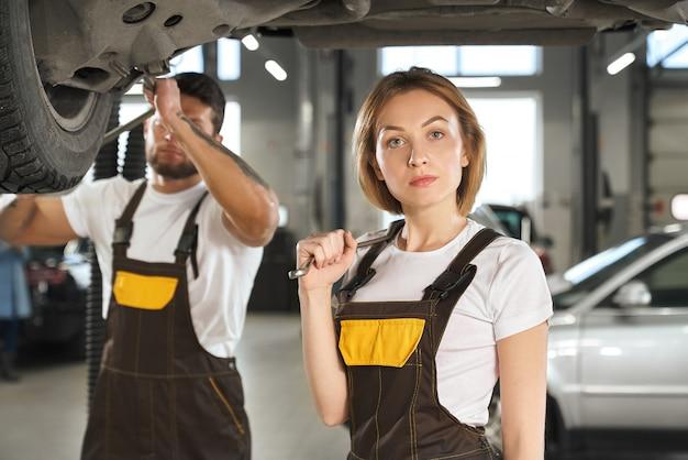 Ernsthafte mechanikerin, die kamera betrachtet und schraubenschlüssel hält