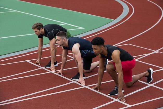 Ernsthafte multiethnische athletengruppe bereit zu laufen