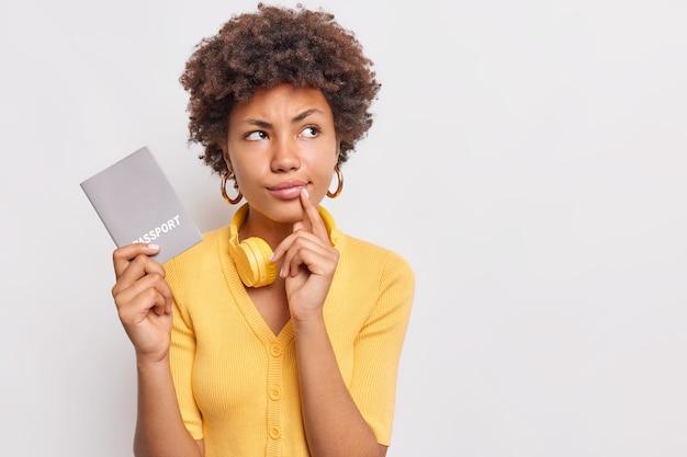 Ernsthafte, nachdenkliche frau mit afro-haar denkt, dass zukünftige reisen nachdenklich wegschauen, trägt einen lässigen gelben pullover hält ein offizielles passdokument und posiert gegen die weiße wand