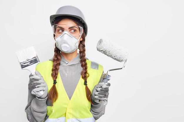 Ernsthafte nachdenkliche frau posiert mit reparaturwerkzeugen