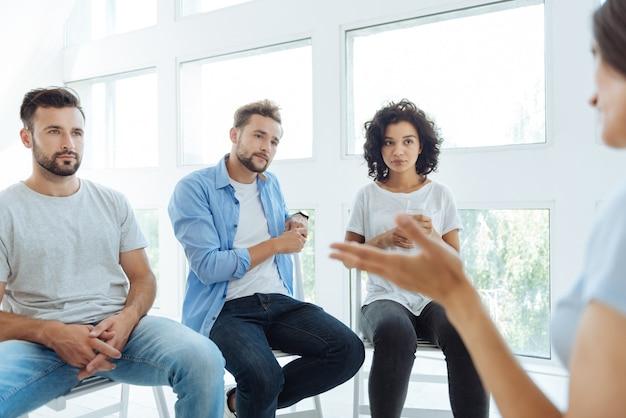 Ernsthafte nette mitglieder der therapiegruppe, die ihrer freundin zuhören und ihre probleme während einer therapiesitzung verstehen