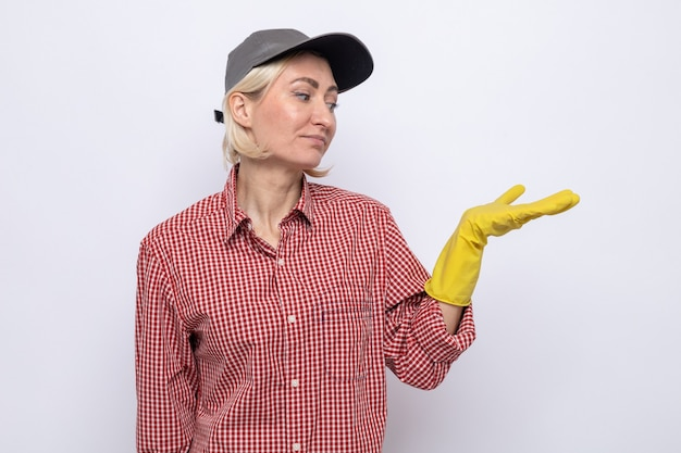 Ernsthafte putzfrau in kariertem hemd und mütze mit gummihandschuhen, die ihren arm anschaut und etwas präsentiert