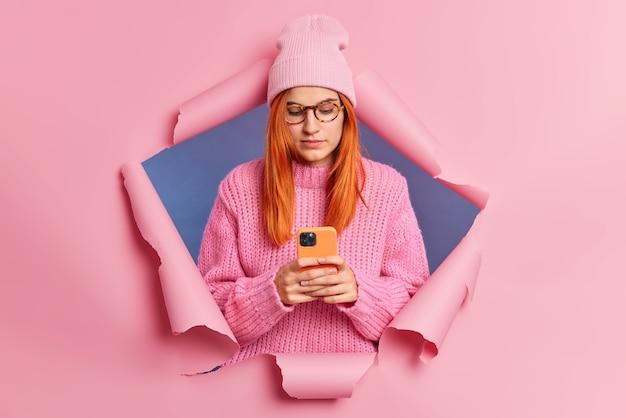 Ernsthafte rothaarige frau hält handy und plaudert mit freunden in sozialen netzwerken liest nachrichten in e-mail trägt rosa hut und strickpullover verbunden mit drahtlosem internet bricht durch papierwand