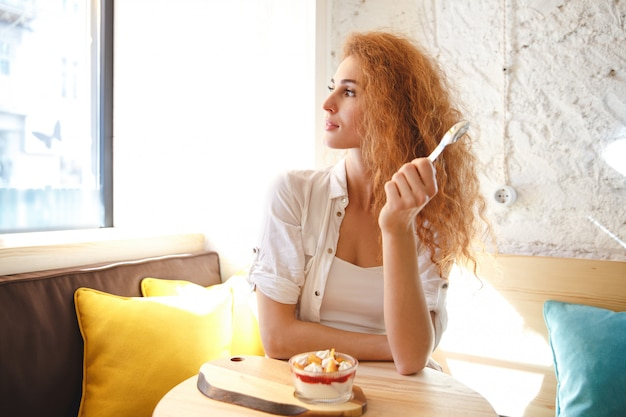 Ernsthafte rothaarige junge dame, die im café beim essen des nachtischs sitzt.