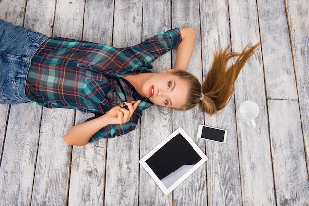 Ernsthafte ruhige frau mit tablette, brille, telefon und tasse, die auf dem floar liegen