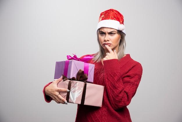 Ernsthafte schauende frau in sankt-hut, die weihnachtsgeschenke hält.