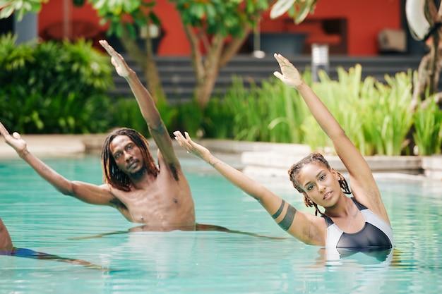 Ernsthafte schöne fit junge leute, die im schwimmbad stehen und seitenbiegungen machen, um sich aufzuwärmen