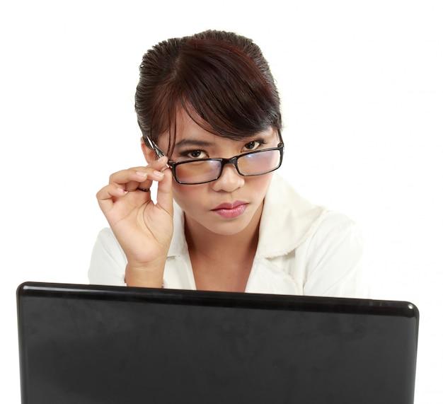Ernsthafte schöne junge frau, die mit ihrem laptop arbeitet