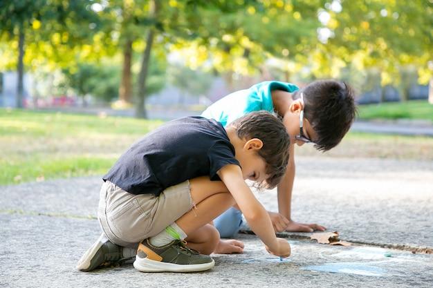 Ernsthafte schwarzhaarige jungen, die mit bunten kreiden sitzen und zeichnen. seitenansicht. konzept für kindheit und kreativität