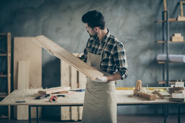 Ernsthafte selbstbewusste arbeiterreparaturmöbel halten hölzernen planbretttest, der schnitzblick in hausgarage glättet