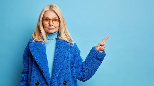 Ernsthafte selbstbewusste blonde frau trägt eine brille und einen wintermantel, der auf den kopierraum zeigt