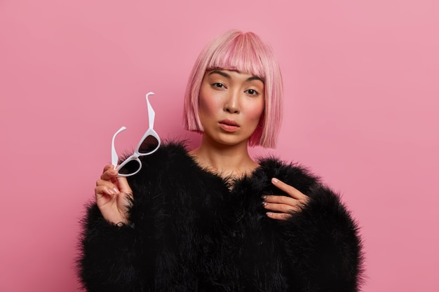 Ernsthafte selbstbewusste dame mit natürlichem make-up, bob-frisur, rosa fransen, nimmt die sonnenbrille ab, trägt einen warmen, flauschigen schwarzen pullover, bewundert etwas,