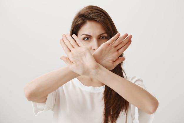 Ernsthafte, selbstbewusste frau macht eine kreuzgeste, um jemanden abzulehnen oder aufzuhalten