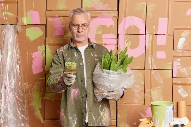 Ernsthafte selbstbewusste maler wartungsarbeiter hält pinsel und malt wände designs innenraum des raumes verwendet arbeitsgeräte bewegt sich in neuen haus trägt kaktus. professioneller dekorateur renoviert haus