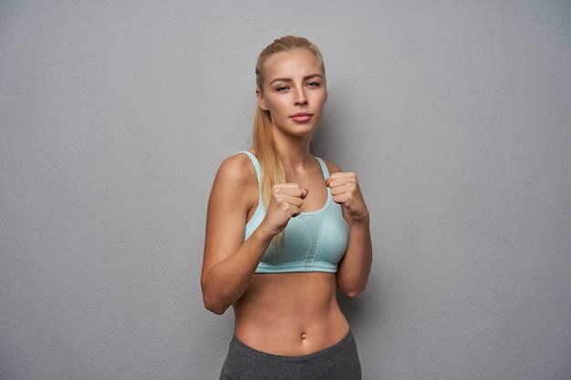Ernsthafte sportliche junge langhaarige blonde frau in sportkleidung, die über hellgrauem hintergrund in defensiver position steht, hände erhoben hält und zur kamera mit gefalteten lippen schaut
