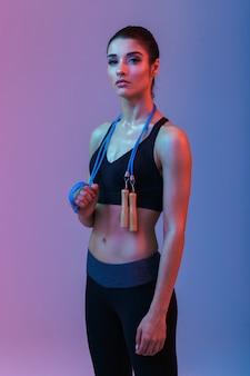 Ernsthafte starke junge sportfrau, die springseil hält.