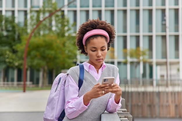 Ernsthafte studentin hält handy-chats online durchsucht das internet in freizeitkleidung trägt rucksack-posen draußen gegen modernes stadtgebäude geht von der universität nach der vorlesung