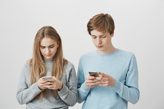 Ernsthafte süße geschwister benutzen handys. messaging für blonde männer und frauen