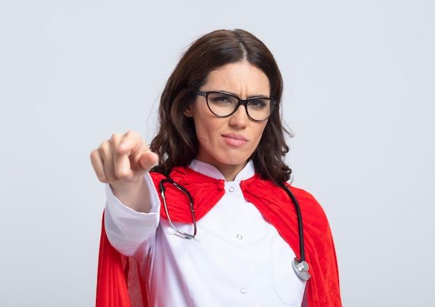 Ernsthafte superfrau in arztuniform mit rotem umhang und stethoskop in optischen brillen zeigt vorne isoliert auf weißer wand