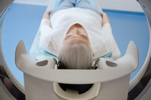 Ernsthafte unglückliche frau im alter, die gesundheitliche probleme hat und sich einem ct-scan unterzieht, während sie ein krankenhaus besucht