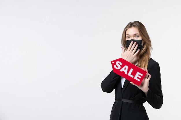 Ernsthafte unternehmerin im anzug, die ihre medizinische maske trägt und den verkauf zeigt, der auf isoliertem weiß eine stille geste macht