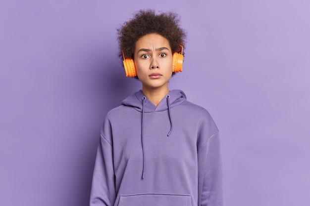 Ernsthafte unzufriedene afroamerikanische frau mit lockigem haar sieht verwirrt aus, wütend zu sein, trägt stereokopfhörer und hört musik, während sie in einem hoodie auf der straße spazieren geht.