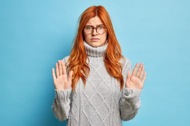 Ernsthafte unzufriedene rothaarige frau zeigt stop-geste hebt die handflächen in richtung gestrickter grauer pullover.
