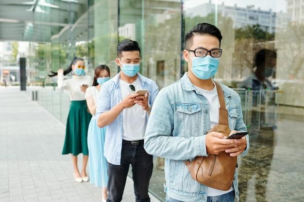 Ernsthafte vietnamesische jugendliche in schutzmasken, die wegen einer pandemie vor dem laden hintereinander stehen