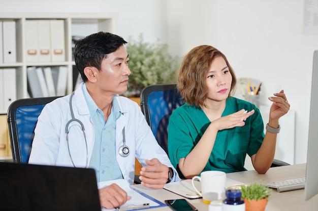 Ernsthafte vietnamesische mediziner, die eine online-konferenz mit kollegen haben und schwierige fälle besprechen