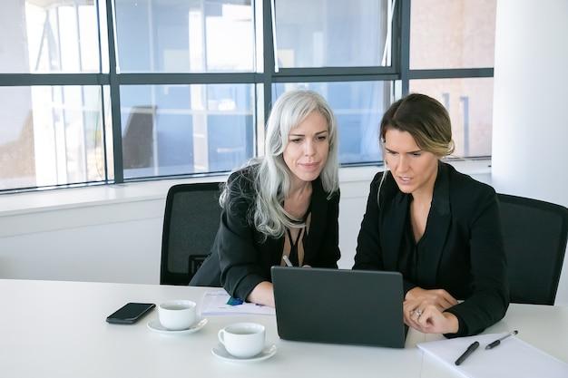 Ernsthafte weibliche profis, die laptopanzeige beim sitzen am tisch mit tassen kaffee und papieren im büro betrachten. vorderansicht. teamwork und kommunikationskonzept