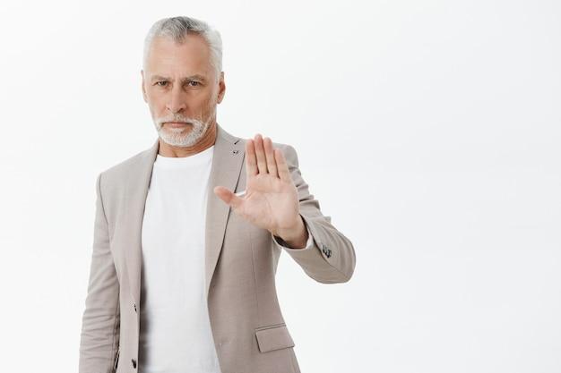Ernsthafter älterer geschäftsmann, der hand in stoppgeste hebt, missbilligt, handlung verbietet
