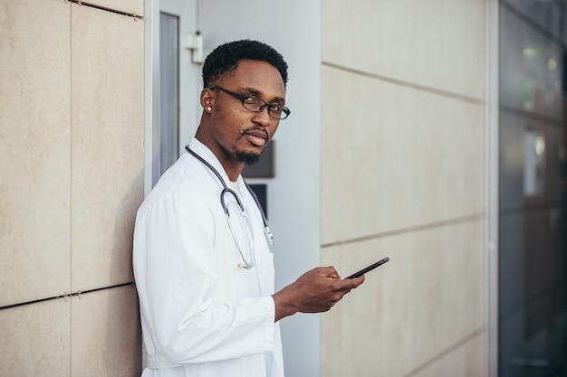 Ernsthafter afroamerikanischer arzt, in der nähe der klinik, in einem weißen medizinischen kittel schaut in die kamera und hält ein mobiltelefon, um mit patienten zu sprechen